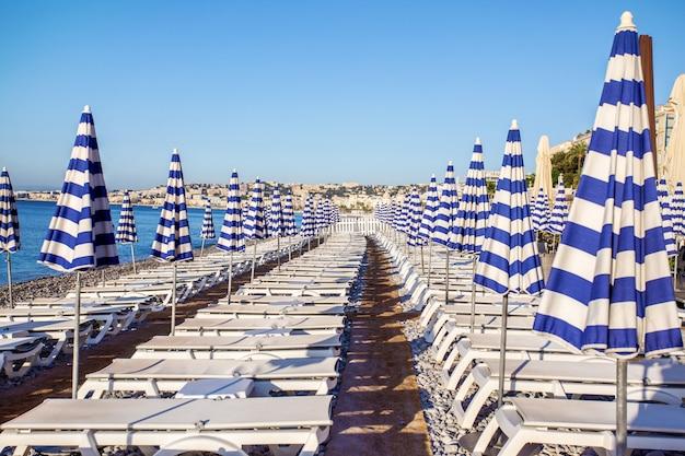 Widok błękitni pasiaści parasole na plaży w ładnym, cote d'azur, południowy francja