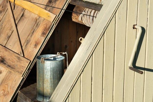 Widok boczny rosyjskiej tradycyjnej studni z otwartymi drzwiami i metalowym wiadrem głupca