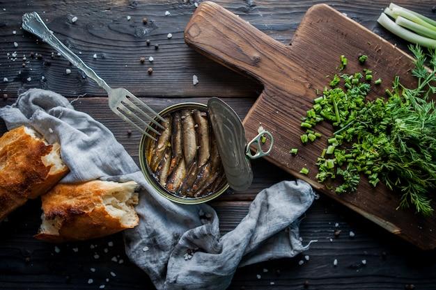 Widok boczny szprot w puszce z posiekanymi zieleniami oraz widelcem i deską do krojenia