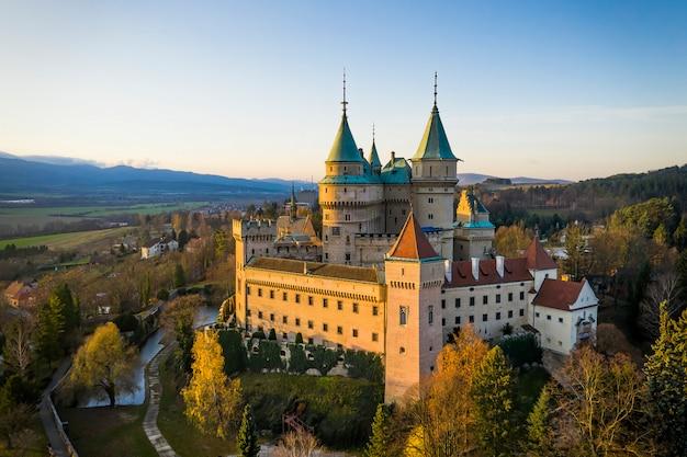 Widok boczny zamku bojnice z jedną ścianą skąpaną w pięknym świetle poranka.