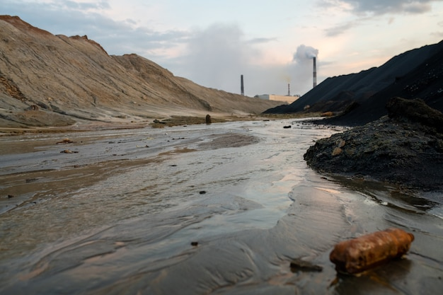 Widok brudnej drogi z błotem i dużymi kałużami lub rzeką otoczoną zanieczyszczonymi wzgórzami i fabrykami przemysłowymi wyczerpującymi toksyczne opary