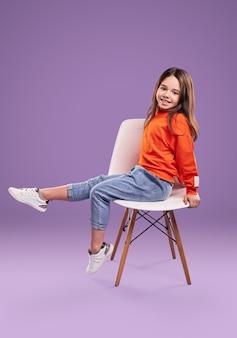 Widok całego ciała z boku uśmiechniętej dziewczynki w pomarańczowej bluzie i dżinsach z białymi trampkami siedzi na krześle w studio na fioletowym tle