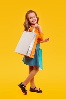 Widok całego ciała z boku zachwyconej małej zalotnej dziewczyny w kolorowych ubraniach, niosącej torby na zakupy i patrzącej, ciesząc się zakupami podczas wyprzedaży