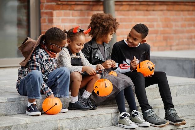Widok całej długości na grupę afroamerykańskich dzieci trzymających halloweenowe wiadra, siedząc na kraw...
