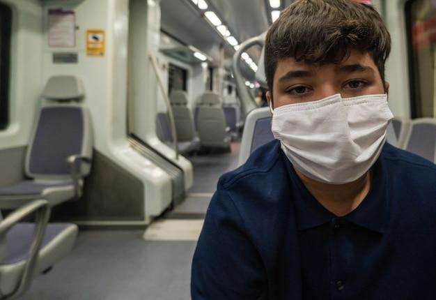 Widok chłopca w masce wewnątrz wagonu metra w maladze podczas pandemii.