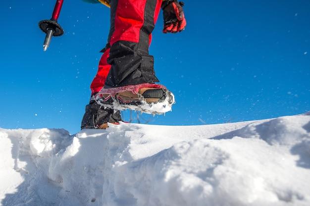 Widok chodzenia po śniegu z butami śnieżnymi i kolcami do butów w zimie