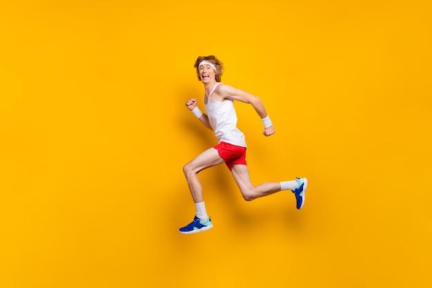 Widok ciała funky zadowolony zmotywowany facet skaczący bieg