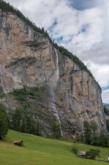 Widok closeup wodospad staubbach wchodzą w góry, dolina wodospadów w parku narodowym lauterbrunnen, szwajcaria, europa. letni krajobraz, słoneczna pogoda, dramatyczne błękitne niebo i słoneczny dzień
