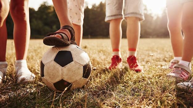 Widok cząstek dzieci, które stoją w polu w słoneczny dzień z piłką nożną.