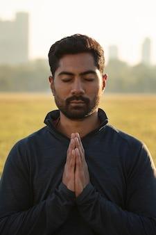 Widok człowieka medytującego na zewnątrz z przodu