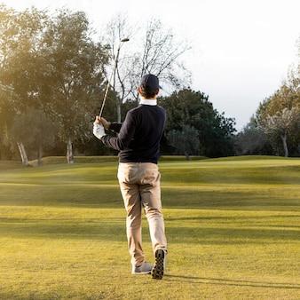 Widok człowieka na trawiastym polu golfowym z tyłu