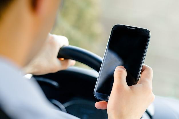 Widok człowieka siedzącego na fotelu kierowcy i patrzącego na ciemny ekran smartfona z tyłu