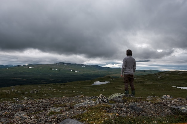 Widok człowieka stojącego na skalistym wzgórzu z burzowymi chmurami