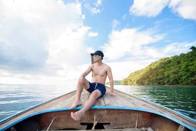 Widok człowieka w strój kąpielowy, ciesząc się na tradycyjnej tajskiej łodzi longtail nad piękną górą i oceanem