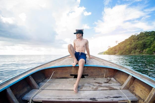 Widok człowieka w stroju kąpielowym, ciesząc się na tajskim tradycyjnym longtail łodzi nad piękne góry i ocean, wyspy phi phi, tajlandia