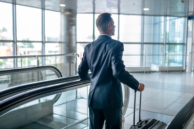 Widok człowieka z walizką na schodach ruchomych z tyłu