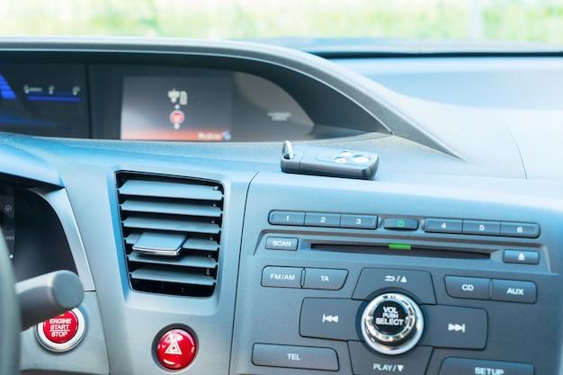 Widok deski rozdzielczej nowoczesnego samochodu z silnikiem rozruchowym i kluczykami