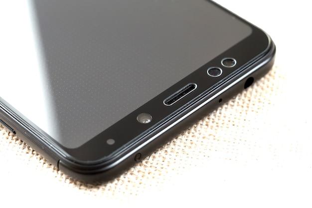 Widok detai z bliska kamery przedniej telefonu komórkowego, czujników i głośnika. nowoczesna technologia i koncepcja projektowania smartfonów.