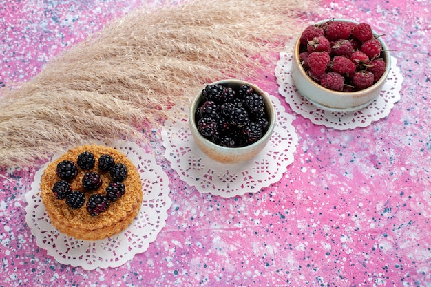 Widok do połowy góry małe jeżynowe ciasto z malinami i świeżymi jeżynami na jasnoróżowym tle.