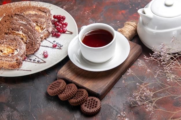 Widok do połowy góry pyszne bułeczki biszkoptowe z ciasteczkami i herbatą na ciemnym stole ze słodyczami