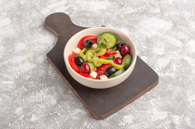Widok do połowy góry sałatka ze świeżych warzyw z pokrojonymi ogórkami, pomidorami, oliwą i białym serem wewnątrz talerza na szarym biurku