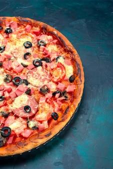 Widok do połowy góry upiekł na niebieskim biurku pyszną pizzę z kiełbaskami z oliwek i serem.