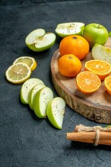 Widok dolnej połowy pokrojonych jabłek i mandarynek na okrągłej desce drewnianej cynamonów związanych liną plasterkami cytryny na ciemnym stole