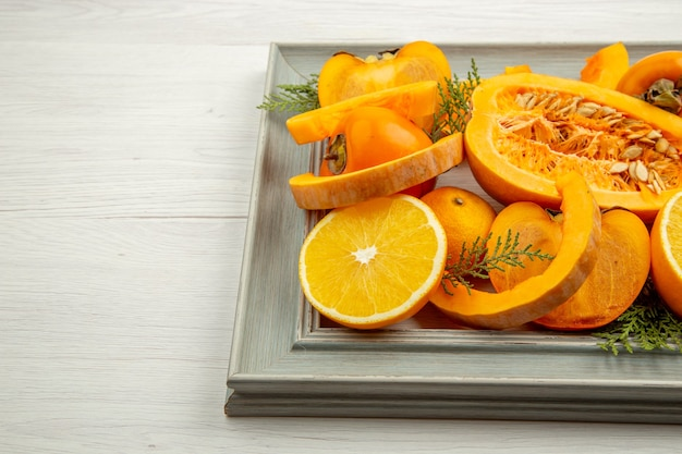 Widok dolnej połowy pół dyni piżmowej pokrojone w pomarańczowe mandarynki persimmons na ramie na białym stole wolne miejsce
