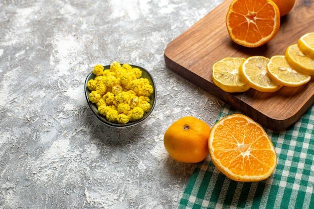 Widok dolnej połowy pomarańczy plasterki cytryny na desce drewnianej żółte cukierki w misce na szarej powierzchni