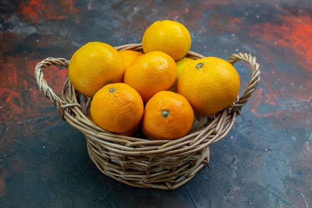 Widok dolnej połowy świeżych mandarynek w wiklinowym koszu na ciemnoczerwonym stole