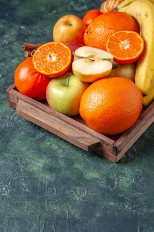 Widok dolnej połowy świeżych owoców i laski cynamonu na drewnianej tacy na ciemnym tle wolnej przestrzeni