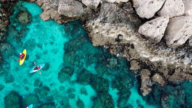 Widok drona z drona ludzie kajakują się w morzu w pobliżu gór na wyspie cypr ayia napa
