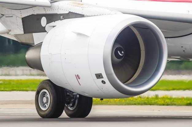 Widok dużego nowoczesnego samolotu na ogromny silnik i podwozie, światło słoneczne.