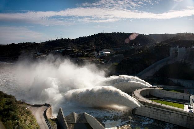 Widok dwóch potężnych strumieni wody na zaporze alqueva, portugalia.