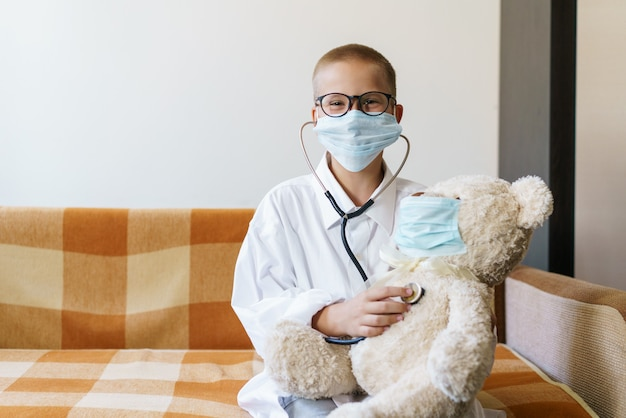 Widok dziecka bawiącego się w lekarza lub pielęgniarkę z misiem w słońcu w domu szczęśliwy chłopiec słucha...