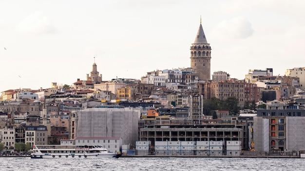 Widok dzielnicy z budynkami mieszkalnymi i wieżą galata w stambule, cieśnina bosfor z ruchomą łodzią na pierwszym planie, turcja