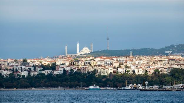 Widok dzielnicy z budynkami mieszkalnymi w stambule, cieśnina bosfor na pierwszym planie, w oddali meczet sułtana ahmeda, turcja
