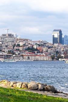 Widok dzielnicy z mieszkalnymi i wysokimi nowoczesnymi budynkami w stambule, cieśnina bosfor z łodziami, ludzie odpoczywający na brzegu, turcja