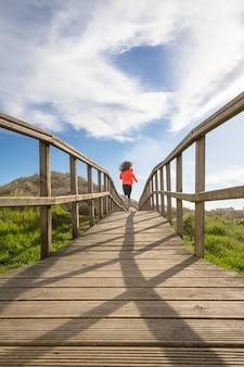 Widok dziewczyny biegającej po drewnianej promenadzie z tyłu