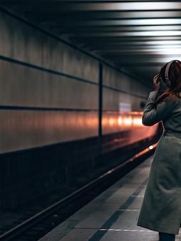 Widok dziewczyny w szarym płaszczu ze słuchawkami na głowie z tyłu. podświetlenie reflektorów pociągu oświetla sylwetkę dziewczyny w ciemnym tunelu