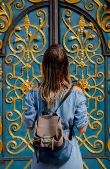 Widok dziewczyny z plecakiem stojącej w pobliżu pięknych drzwi z tyłu