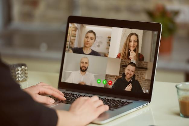 Widok ekranu laptopa przez ramię kobiety. dziewczyna składa oświadczenie dla swoich kolegów na odprawie online