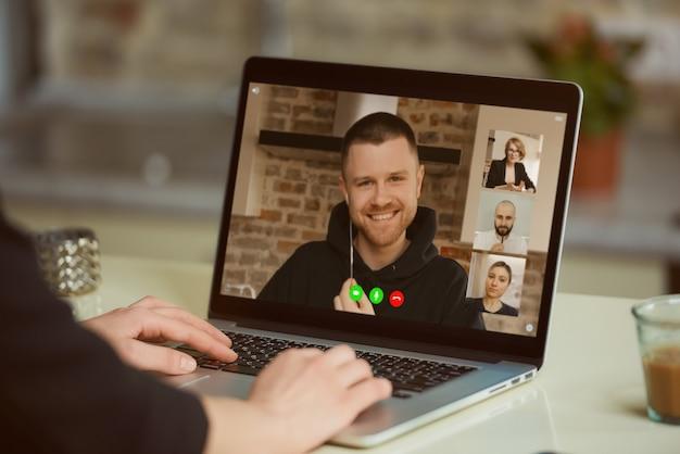 Widok ekranu laptopa przez ramię kobiety. dziewczyna słucha wypowiedzi swoich kolegów na odprawie online