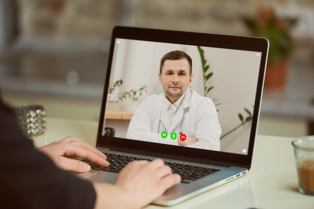 Widok ekranu laptopa przez ramię kobiety.