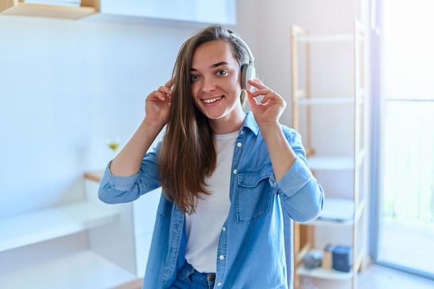 Widok ekranu portretowego uśmiechniętej słodkiej młodej dziewczyny z bezprzewodowymi słuchawkami, siedzącej w domu i rozmawiającej podczas rozmowy wideo na komputerze