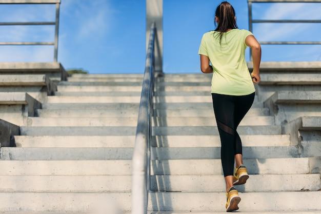 Widok energicznej młodej brunetki ubranej w żółty t-shirt i czarne spodnie bieganie po schodach z tyłu.
