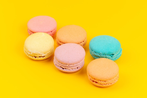 Widok frotn francuskie macarons pyszne i pieczone okrągłe uformowane na żółtym biurku, kolor ciasto biszkopt
