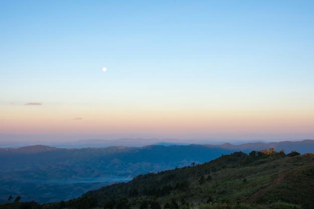 Widok górski z księżycem w ranku.