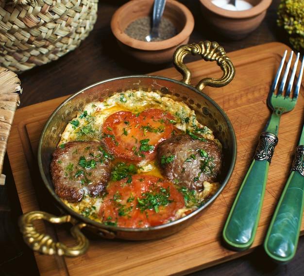 Widok gotowanych jajek z przodu z czerwonymi pomidorami wewnątrz metalowej patelni na brązowym drewnianym biurku