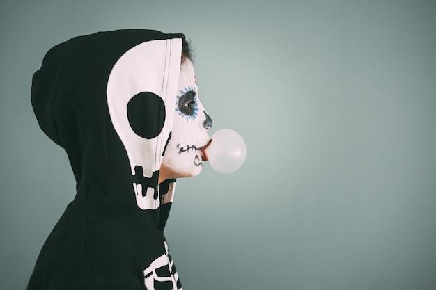 Widok grofile dziewczyny z makijażem i kostiumem martwej dziewczyny, który robi bąbelki z gumą do żucia